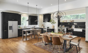 Wide kitchen and dining area with black cabinets.